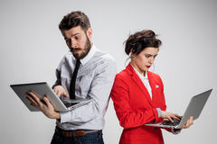 El hombre de negocios y la empresaria jovenes con los ordenadores portátiles que comunican en fondo gris Foto de archivo libre de regalías