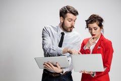 El hombre de negocios y la empresaria jovenes con los ordenadores portátiles que comunican en fondo gris Imágenes de archivo libres de regalías
