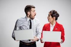 El hombre de negocios y la empresaria jovenes con los ordenadores portátiles que comunican en fondo gris Imagen de archivo libre de regalías