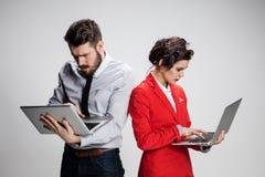 El hombre de negocios y la empresaria jovenes con los ordenadores portátiles que comunican en fondo gris Fotos de archivo