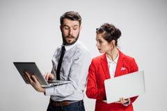 El hombre de negocios y la empresaria jovenes con los ordenadores portátiles que comunican en fondo gris Fotografía de archivo libre de regalías