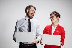El hombre de negocios y la empresaria jovenes con los ordenadores portátiles que comunican en fondo gris Imagen de archivo