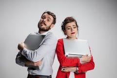 El hombre de negocios y la empresaria jovenes con los ordenadores portátiles que presentan en fondo gris Imagen de archivo libre de regalías