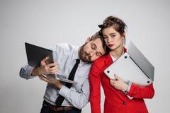 El hombre de negocios y la empresaria jovenes con los ordenadores portátiles que presentan en fondo gris Fotografía de archivo libre de regalías