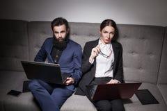 El hombre de negocios y la empresaria se vistieron en traje y con el ordenador portátil, p Imagenes de archivo