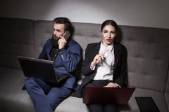 El hombre de negocios y la empresaria se vistieron en traje y con el ordenador portátil, p Imagen de archivo libre de regalías