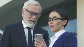 El hombre de negocios y la mujer que usa el smartphone, secretaria está de acuerdo con orden del día con el jefe almacen de video