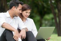 El hombre de negocios y la mujer utilizan el ordenador portátil en parque, se sientan en hierba juntos foto de archivo