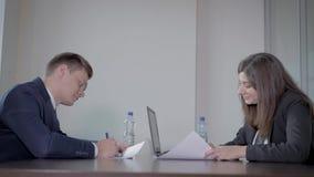 El hombre de negocios y los documentos de la muestra y del intercambio de la mujer entonces sacuden las manos en oficina almacen de metraje de vídeo