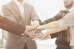 El hombre de negocios y su negocio combinan con las manos abrochadas juntas para mostrar su unidad imagen de archivo