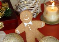 El hombre de pan de jengibre precioso está jugando con las bolas de la Navidad imágenes de archivo libres de regalías