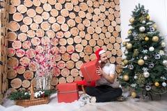 El hombre de Papá Noel con la caja roja se sienta en el árbol de navidad Foto de archivo libre de regalías