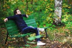 El hombre de pelo oscuro atractivo en chaqueta y vaqueros se sienta en un banco n Imagen de archivo libre de regalías