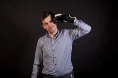 El hombre de pelo oscuro en una camisa de tela escocesa con los guantes de boxeo en sus manos se bate foto de archivo