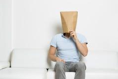 El hombre de pensamiento con la cara cubrió sentarse en el sofá. Fotografía de archivo