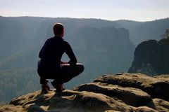 El hombre de reclinación en la cima de la roca con la vista aérea del valle brumoso profundo grita Fotos de archivo