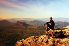 El hombre de reclinación en la cima de la roca con la vista aérea del valle brumoso profundo grita Imagen de archivo