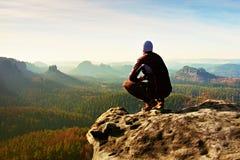 El hombre de reclinación en la cima de la roca con la vista aérea del valle brumoso profundo grita Fotografía de archivo