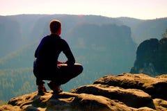 El hombre de reclinación en la cima de la roca con la vista aérea del valle brumoso profundo grita Imágenes de archivo libres de regalías