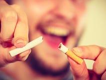 El hombre de Smilling está rompiendo un cigarrillo Fotos de archivo