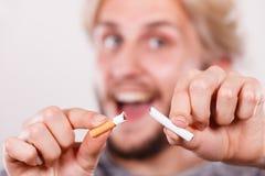 El hombre de Smilling está rompiendo un cigarrillo Fotos de archivo libres de regalías