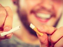 El hombre de Smilling está rompiendo un cigarrillo Imágenes de archivo libres de regalías