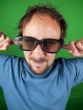El hombre de treinta años con los vidrios 3d tiene demasiado miedo de mirar Imagen de archivo libre de regalías