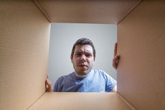 El hombre decepcionado joven está mirando en el regalo dentro de la caja de cartón imagenes de archivo