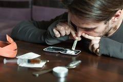El hombre del adicto huele la cocaína de un espejo fotografía de archivo libre de regalías