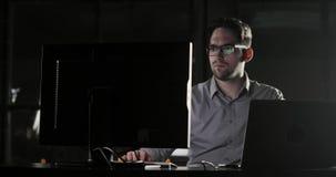 El hombre del administrador de sistema está trabajando en la oficina tarde en el tiempo suplementario de la noche almacen de metraje de vídeo