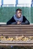 El hombre del adolescente adentro relaja postura en banco de madera del jardín Imagen de archivo