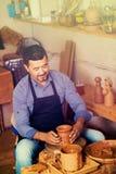 El hombre del artesano que crea el pedazo de cerámica en la cerámica de giro rueda adentro Fotos de archivo libres de regalías