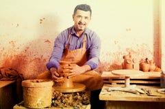 El hombre del artesano que crea el pedazo de cerámica en la cerámica de giro rueda adentro Imágenes de archivo libres de regalías