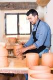 El hombre del artesano que crea el pedazo de cerámica en la cerámica de giro rueda adentro Imagen de archivo libre de regalías