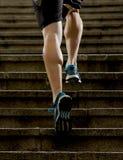 El hombre del atleta con la pierna fuerte muscles la escalera urbana de la ciudad del entrenamiento y del funcionamiento en aptit Fotografía de archivo libre de regalías