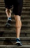 El hombre del atleta con la pierna fuerte muscles la escalera urbana de la ciudad del entrenamiento y del funcionamiento en aptit Imagen de archivo