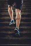 El hombre del atleta con la pierna fuerte muscles la escalera urbana de la ciudad del entrenamiento y del funcionamiento en aptit Foto de archivo