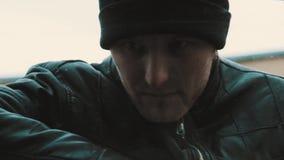 El hombre del bandido en la chaqueta de cuero fuerza a la mujer que se sienta en coche a la ventana abierta almacen de video