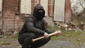 El hombre del bandido en máscara y chaqueta negras con la capilla con el bate de béisbol se sienta en la calle almacen de metraje de vídeo