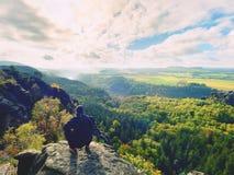 El hombre del caminante toma un resto en pico de montaña El hombre se sienta en el punto de opinión de la cumbre, valle nublado d Fotos de archivo libres de regalías
