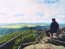 El hombre del caminante toma un resto en pico de montaña El hombre se sienta en el punto de opinión de la cumbre, valle nublado d Foto de archivo