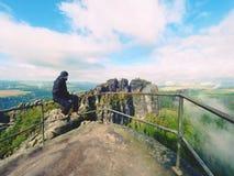 El hombre del caminante toma un resto en pico de montaña El hombre se sienta en el punto de opinión de la cumbre, valle nublado d Imagenes de archivo