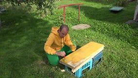 El hombre del carpintero con el cepillo y la pintura sacuden en las manos que pintan la superficie de madera del tablero del tabl almacen de metraje de vídeo