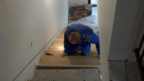 El hombre del carpintero instala el tablero de las escaleras y muestra el finger encima en de la cámara de mirada sonriente almacen de video