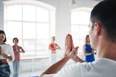El hombre del coche entrena al grupo de mujeres en clase de la yoga Concepto sano de la forma de vida foto de archivo