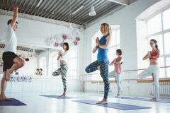 El hombre del coche entrena al grupo de mujeres en clase de la yoga Concepto sano de la forma de vida imagen de archivo libre de regalías