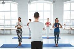 El hombre del coche entrena al grupo de mujeres en clase de la yoga Concepto sano de la forma de vida fotos de archivo libres de regalías