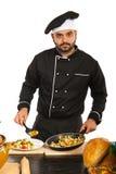 El hombre del cocinero adorna la comida en la placa Imagen de archivo libre de regalías