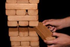 El hombre del concepto del negocio saca una barra de madera en un juego del jenga en un fondo negro imagen de archivo libre de regalías