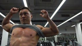 El hombre del culturista está poniendo en el top sin mangas después de un entrenamiento en el gimnasio metrajes